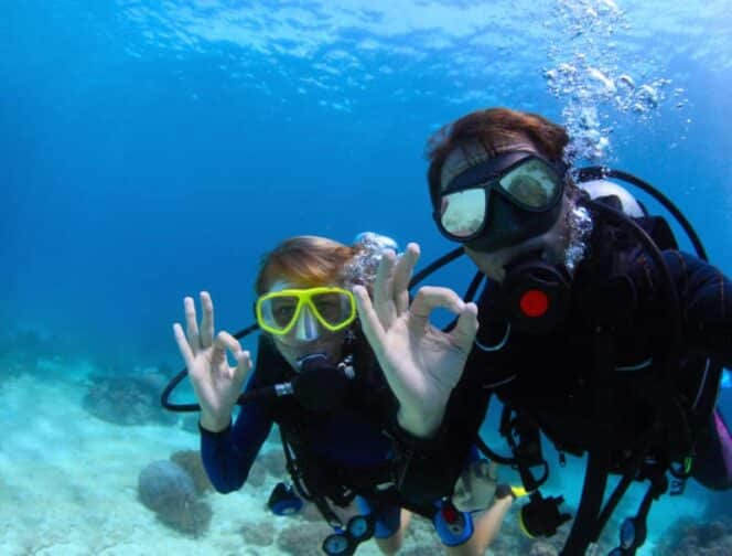 scuba divers underwater showing ok sign, an example of what you can do on a romantic adventure getaway