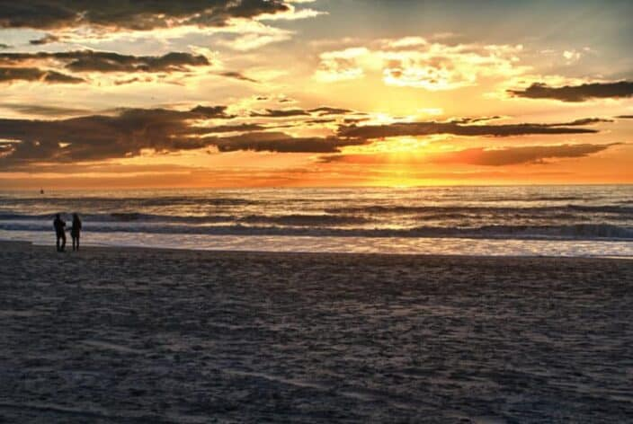 couple walking on the beach at sunrise, an example of a romantic adventure getaway idea