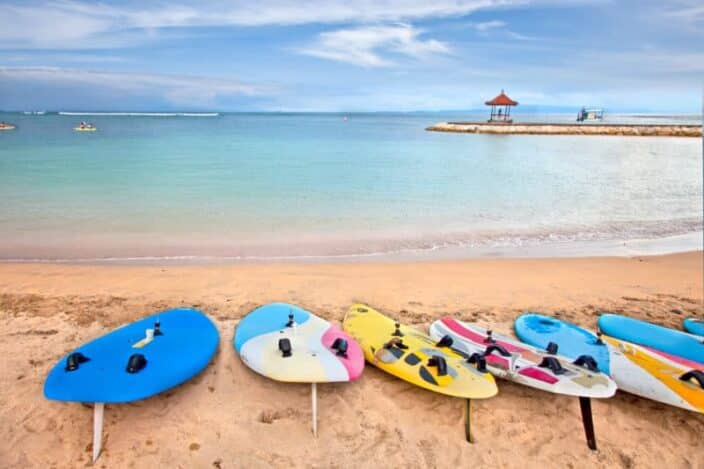 Surf boards on idyllic tropical sand Nusa Dua beach, Bali. An example of an activity you can do during a romantic adventure getaway