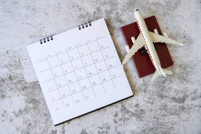 a calendar and toy airplane on top of a small red book on a concrete background