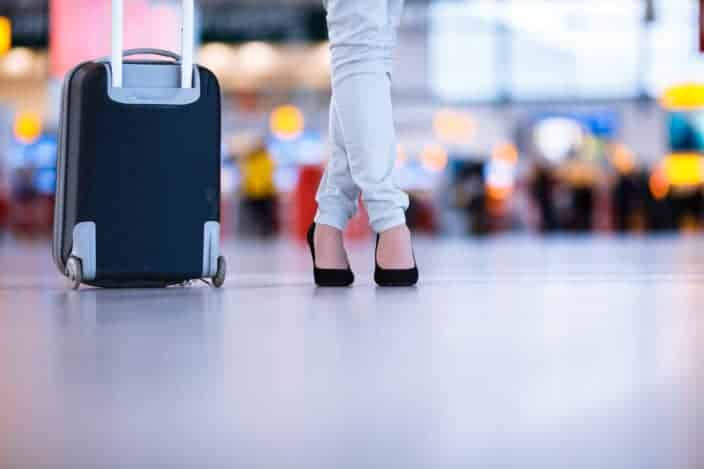view of a woman's legs at the airport with a carry on suitcase packed with travel essentials