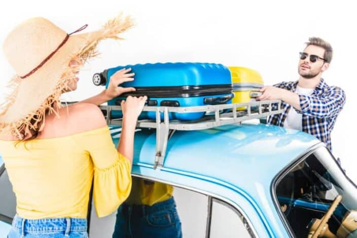 A man and woman strapping down packed suitcases on top of their car for travel