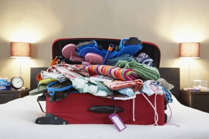 Travel essentials messily stuffed into an overpacked red suitcase on a bed