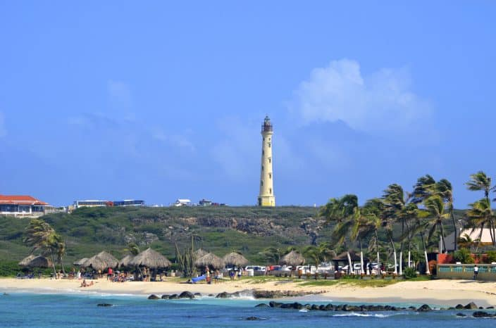 Arashi beach in Aruba with the California Lighthouse on a cliff in the distance, palm trees, sandy coast, blue water, and people enjoying the beach