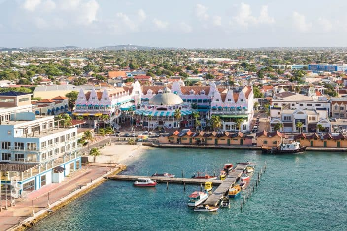 Colorful buildings in Oranjestad, Aruba with a view of the sea and mountains in the background