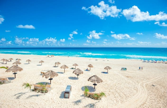 a panorama of Cancun Beach with umbrellas, golden sand, blue water, and skies