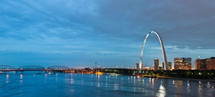 view of the Bay St. Louis, Mississippi in night time with bright lights and the glowing skyline, with the bay and a bridge in the background. The arc sculpture is also in the background.