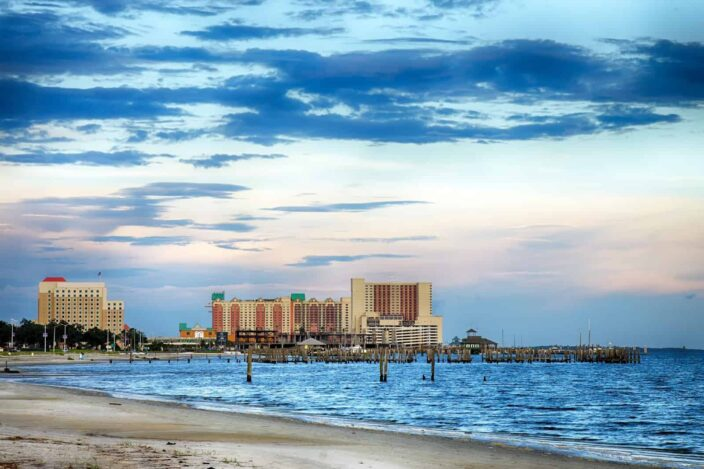 View of the shore in Biloxi, Mississippi with blue waters and casino in the background