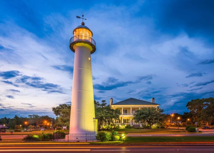 Picture of a lighthouse which has light glowing at the top during the evening, with trees and a big house in the background in Biloxi, Mississippi.
