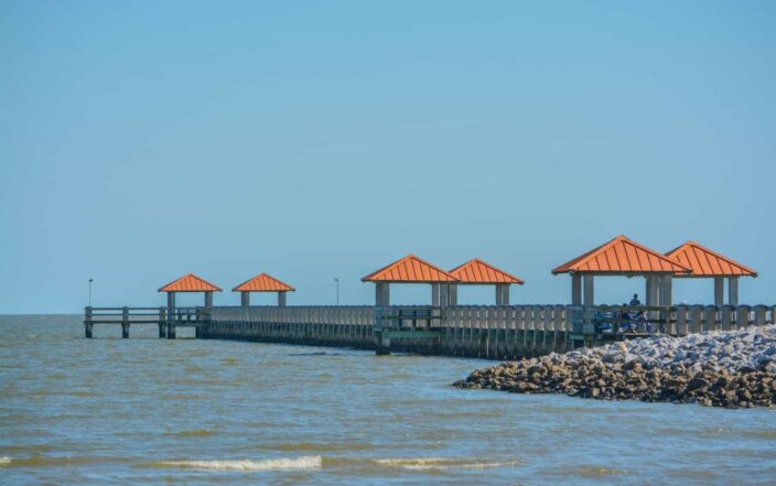 View of the shore with rocks, beachfront, blue skies and waves, with a dock with pergolas with orange roofs in the daylight in Gulfport,  Mississippi.