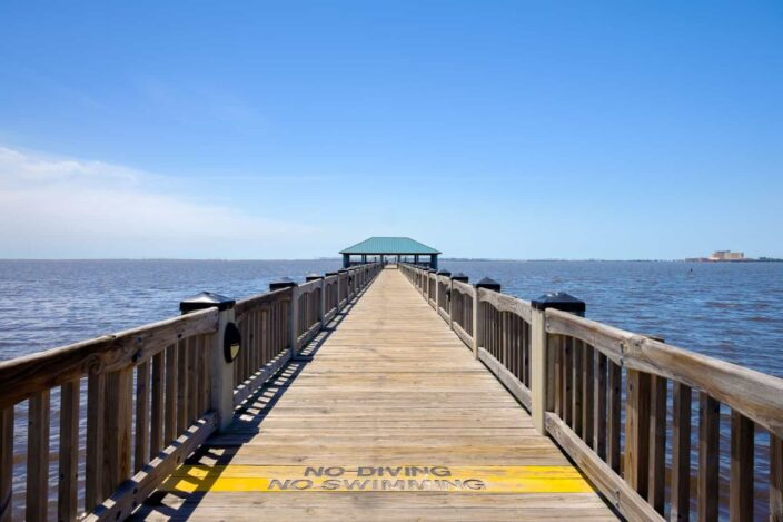 a pier with the words no swimming or diving on it over water in Ocean Springs, Mississippi, with blue skies and dark blue waters
