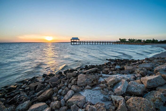 View of the shore at Pass Christian with rocks, beachfront, wood pier and pergola, and the sunset all in one frame.
