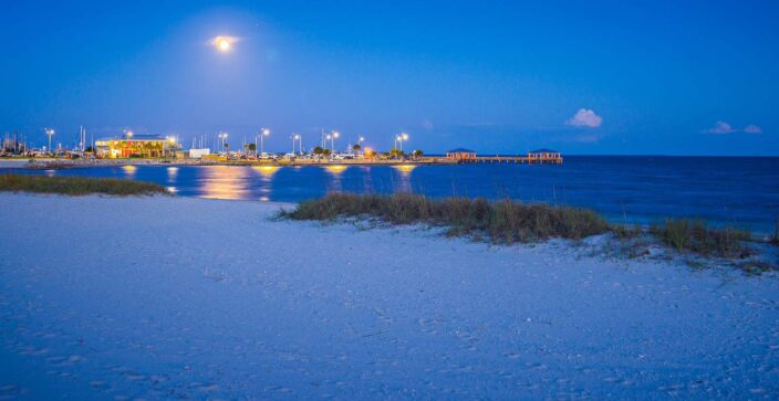 View of the beach with bluish sand, blue waters, and glowing lights of the pier and buildings in the background at night.