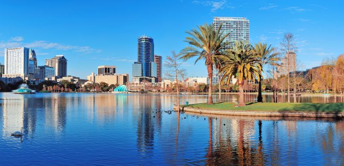 a family friendly vacation in Orlando Lake Eola in the morning with urban skyscrapers and clear blue sky.