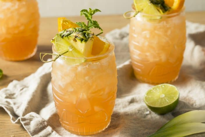 3 goombay smash cocktails in festive clear tiki classes with a garnish of pineapple, orange, and mint on top, sitting on a wooden table with a grey linen cloth on top and a half a lime lying next to them