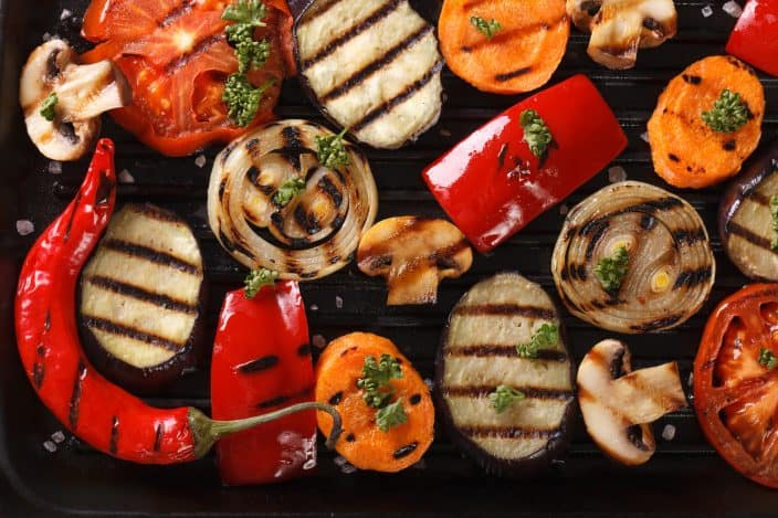 top view of an assortment of grilled vegetables featuring eggplant, carrots, mushrooms, onions, and tomatoes