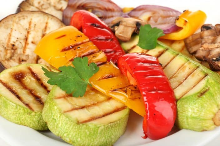Delicious grilled vegetables on plate close-up, featuring eggplant, zucchini, red onions and bell pepper