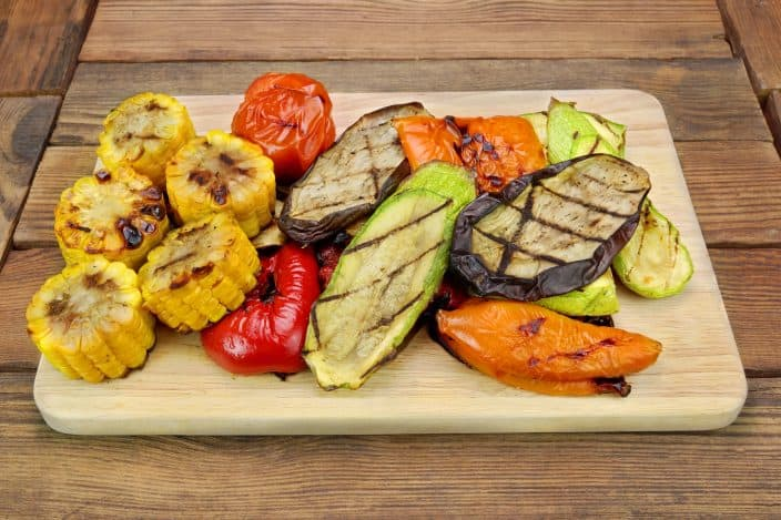 Grilled Vegetables On The Wood Cutting Board featuring Tomato, Bell Pepper, Zucchini, Eggplant, Sweet Corn Rings