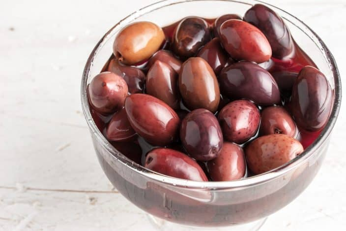 Kalamata olives on the glass bowl on the old wooden table for the making of greek salad skewers