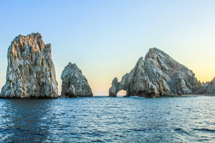 Los Arcos arch rock formation with a sunset sky and reflective water at Lands End in Cabo San Lucas, Mexico.