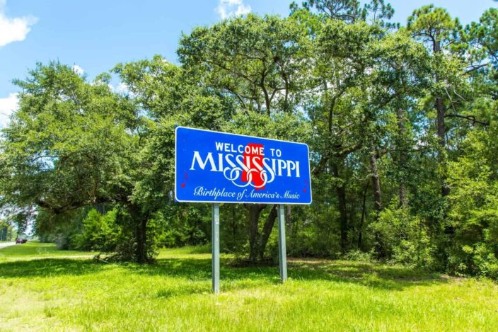 Image of a blue signboard saying Welcome to Mississippi, Birthplace of America's Music in green grass, green trees, and blue skies with clouds in the background.