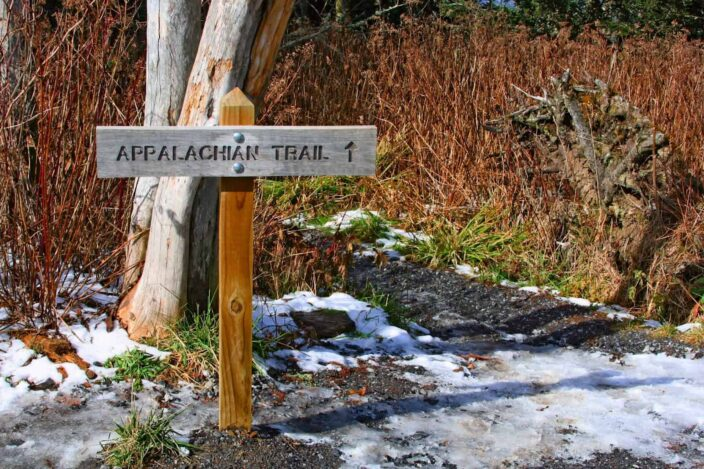 Signboard of the Appalachian trail with snow on the ground and brown bushes with a little bit of green grass in the background.