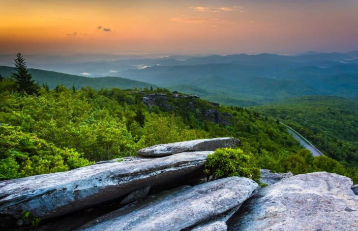 Image of the Blue Ridge Parkway in North Carolina with grey rocks, mountains, and lush green trees during the sunset.