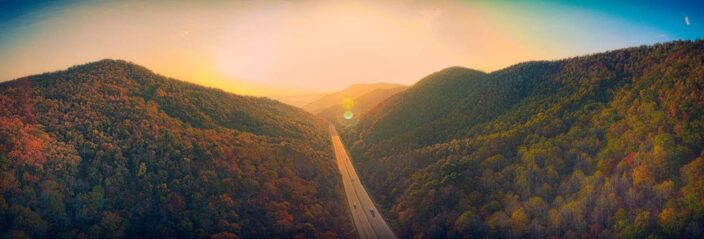 Picture of an endless road going into the sunset with lush green trees and mountains in the surroundings to represent a romantic mountain getaway.