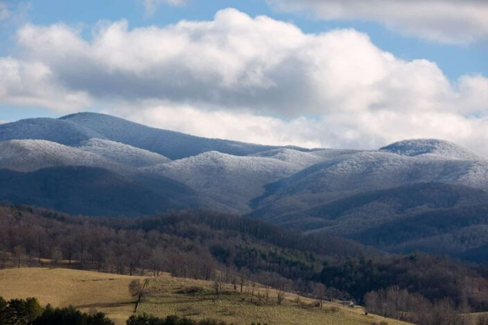 Picture of the Appalachian mountains in the daytime with ice on the mountains and clouds and brown leafless trees in one frame.