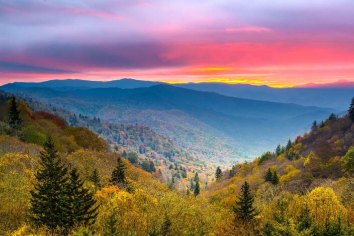 Picture of the smoky mountains at daytime with lush green trees, hills and sunrise all in one frame.