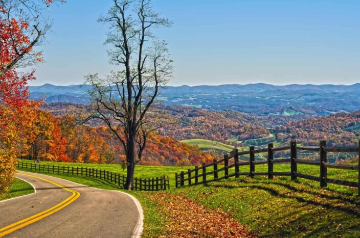 Picture of the Blue Ridge Parkway in Virginia during daytime with mountains, trees and orange leaves all in one frame.