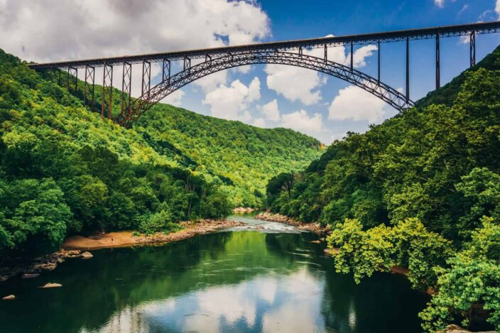 Picture of the River Gorge bridge with green hills on either side and river flowing underneath with blue skies and clouds.