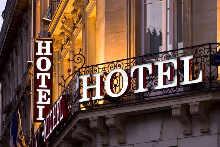 """picture of a hotel window and balcony with a bright sign written """"HOTEL"""" on it."""