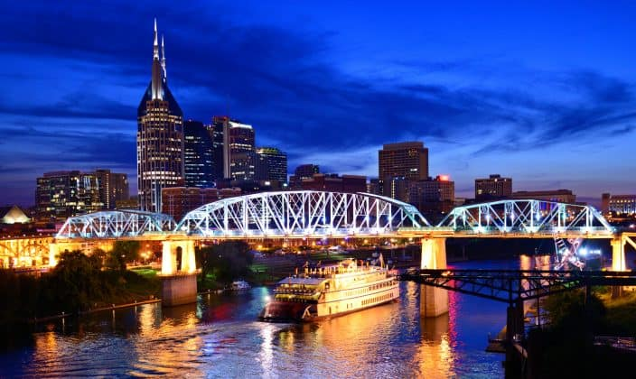 Night View of the Nashville bridge with city lights, skyscrapers, and cruise on the river.