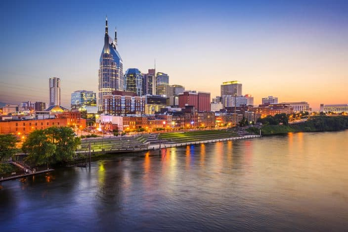 Cityscape view of the city of Nashville with skyscrapers and the Cumberland river with sunset skies.