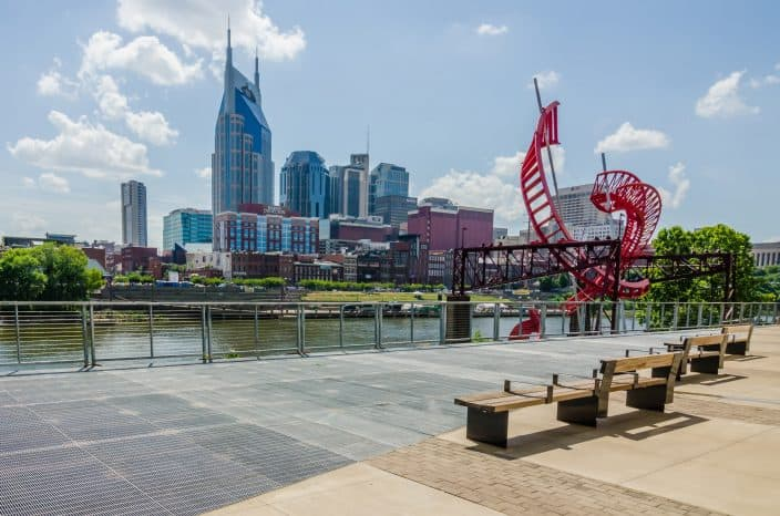 daylight view of Nashville city with skyscrapers, a red helix sculpture, benches, green trees, blue skies, and river in one frame.
