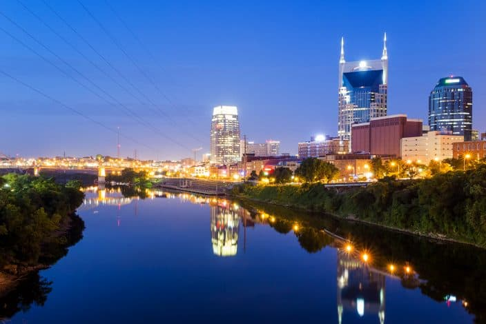 night view of the city of Nashville with river belt and reflection of lights from skyscrapers.