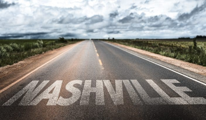 Nashville sign on printed on the clear road with grey skies, clouds, and grass on either side of the road