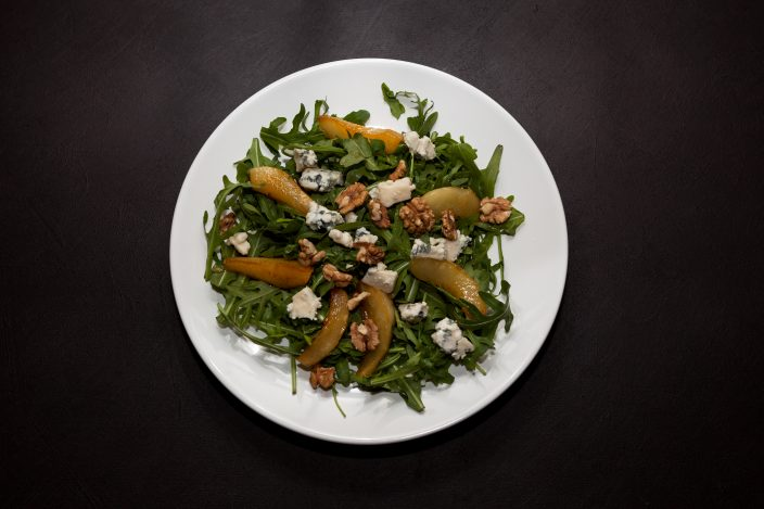 Pear and Blue cheese salad with Arugula, warm caramelized pear, walnuts and blue cheese. Top view, dark background