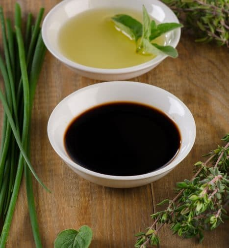Dressing for the pear and blue cheese salad. Olive oil, balsamic vinegar and herbs on a vintage wood background