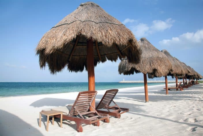 Playa Del Carmen beach in Mexico with palm umbrellas, beach chairs, blue water and skies, and golden sand