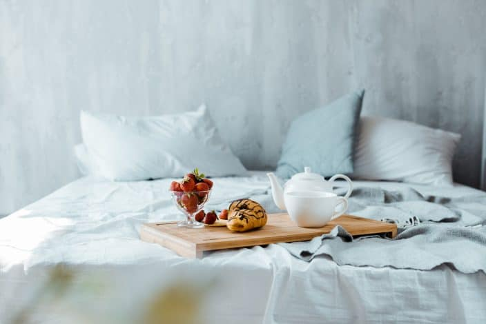 a bed with grey walls and a breakfast platter sitting on the bed to represent a bed and breakfast for travel deals