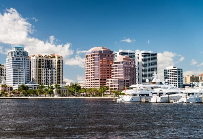 West Palm Beach, Florida. Panoramic city skyline, with skyscrapers, palm trees on the coastline, and yachts in the water, a great day trip from Fort Lauderdale
