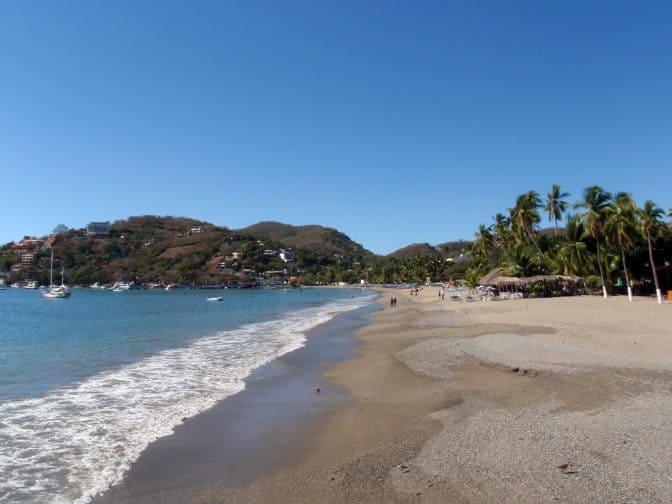 Beautiful tropical sandy beach with boats in the water and hills in the background in Zihautanejo, Mexico