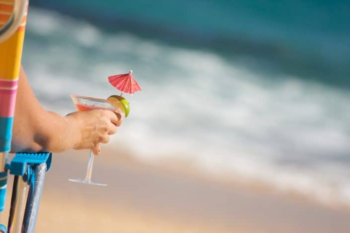 a woman holding a margarita glass with red drink umbrella and a lime sitting in a chair on the beach by the water during her beach day