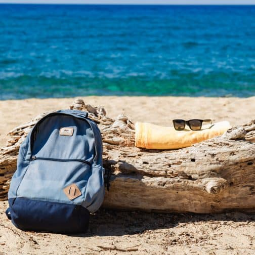 Picture of a blue backpack, towel, and sunglasses on a log with blue seashore and sand in the background.