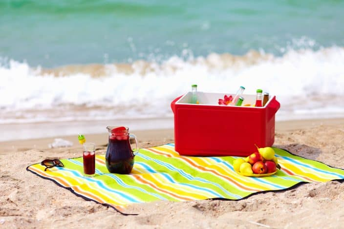 Picture of the beach with icebox placed on a multi-colored sheet with fruits on the side, chilled drink, sunglasses, and the waves all in the background.