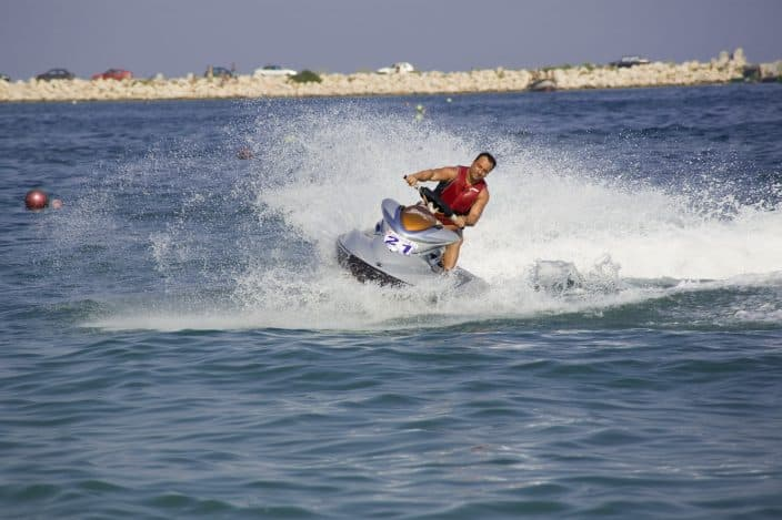 Man jet skiing in the sea leaving a splash of water behind as he moves fast, a fun beach day activity.