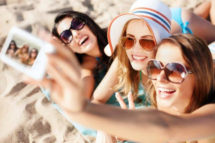 Group of girls taking a selfie on the beach during their beach day.