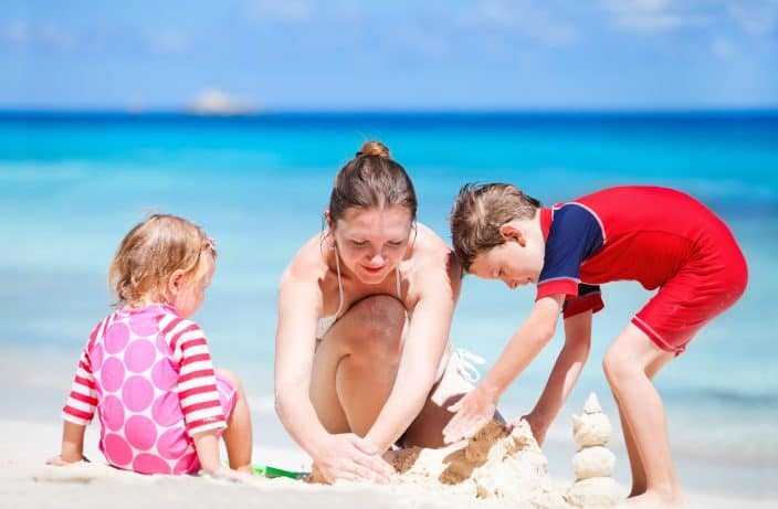 woman building sandcastle with her son in a red swimsuit and daughter in a pink swimsuit during her beach day with blue skies and blue water in the background.